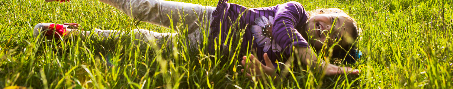 A young girl rolling down a hill in summer
