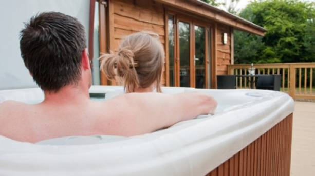 A couple in a hot tub outside a forest lodge in the Yorkshire Wolds